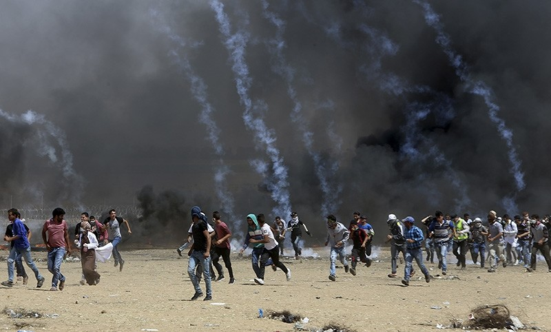 Palestinian protesters run for cover from teargas fired by Israeli troops during a protest at the Gaza Strip's border with Israel, Friday, May 11, 2018. (AP Photo)