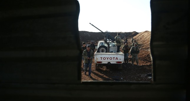 Turkish-backed fighters from the Free Syrian Army hold a position in the Tal Malid area, north of Aleppo, as they prepare to target YPG positions in the area of Afrin, on January 20, 2018. (AFP Photo)