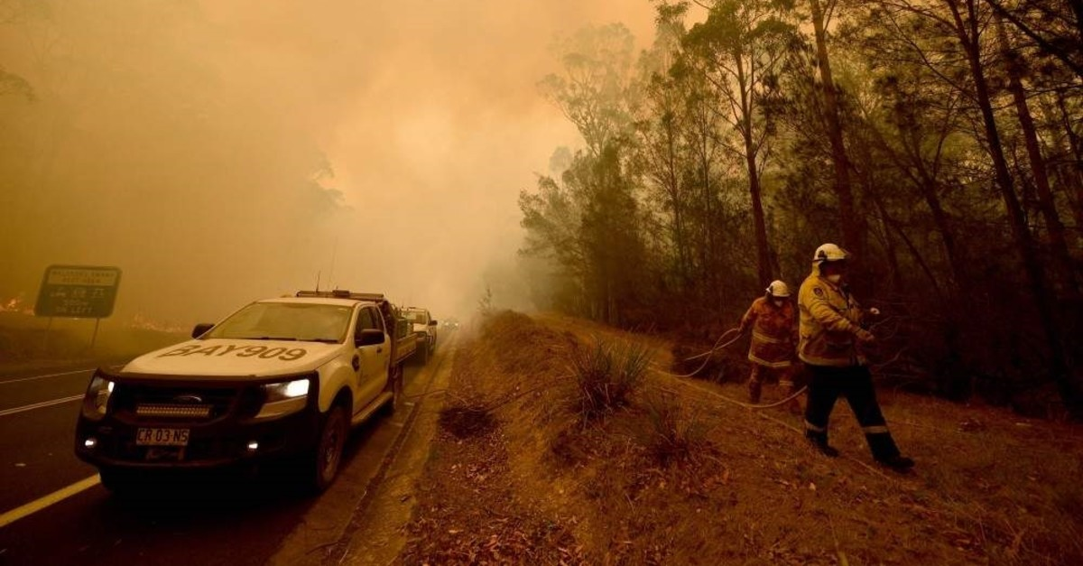 Firefighters tackle a bushfire amid thick smoke in the town of Moruya, south of Batemans Bay, in New South Wales, Jan. 4, 2020. (AFP Photo)
