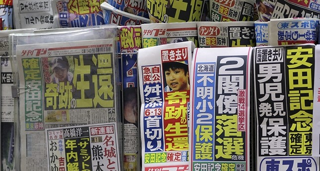 An image of Yamato Tanooka, the missing 7-year-old Japanese boy, is displayed by Japanese newspaper Yukan Fuji being sold at a railway station kiosk in Tokyo (AP Photo)