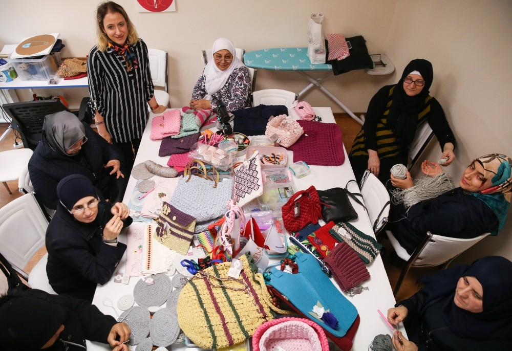 Women sit at a table covered in their handicrafts.