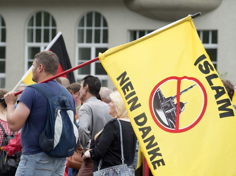 A supporter of the right-wing Patriotic Europeans say NO, holds a flag reading: ,Islam, No Thanks,, during a rally in Erfurt, Germany, June 4, 2016.