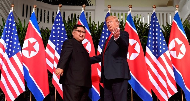 U.S. President Donald Trump R gestures as he meets with North Korea's leader Kim Jong Un L at the start of their historic US-North Korea summit, at the Capella Hotel on Sentosa island in Singapore on June 12, 2018. AFP Photo