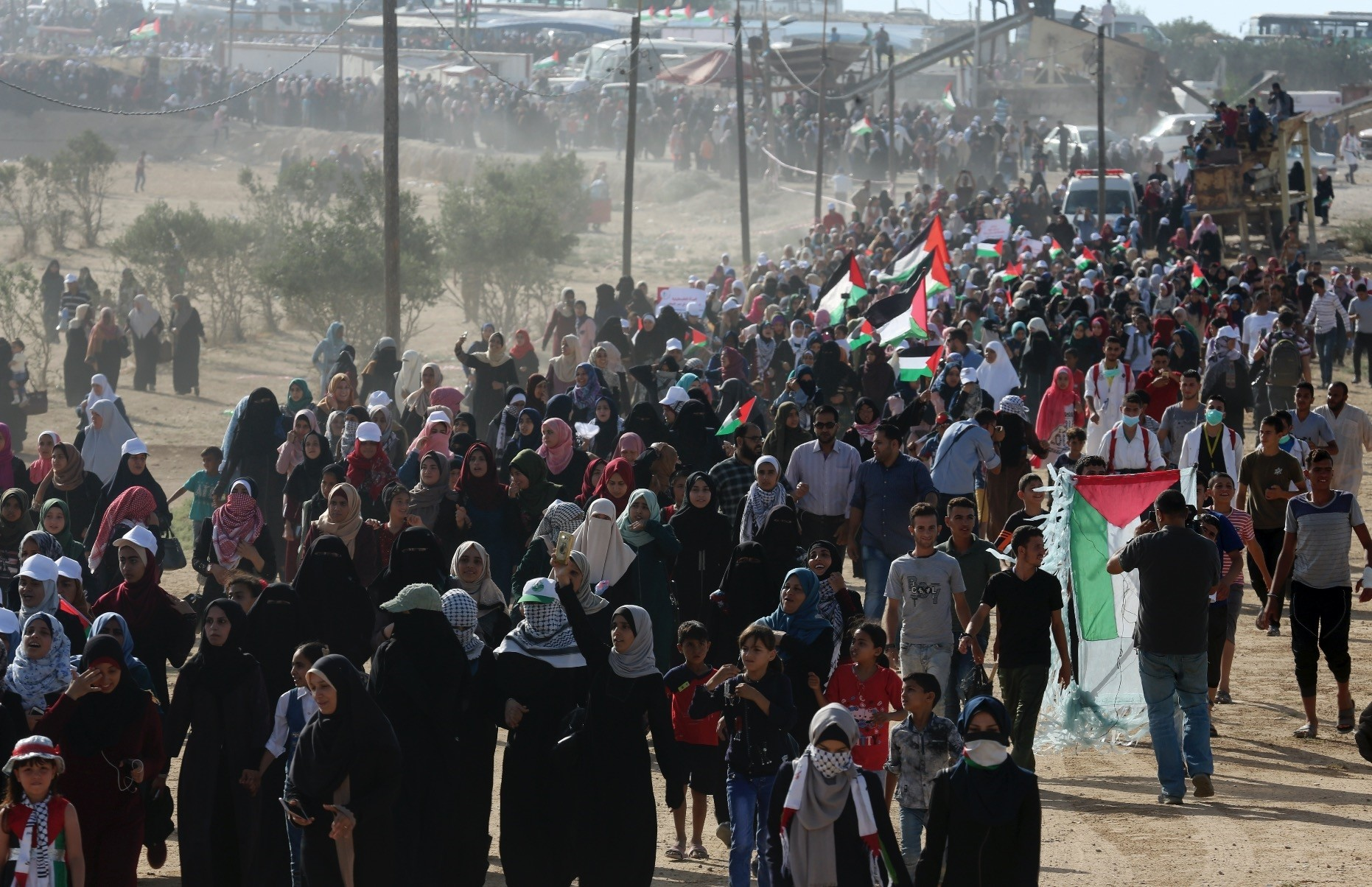 Palestinian women wave their national flags while marching toward the Gaza Stripu2019s border with Israel, July 3.