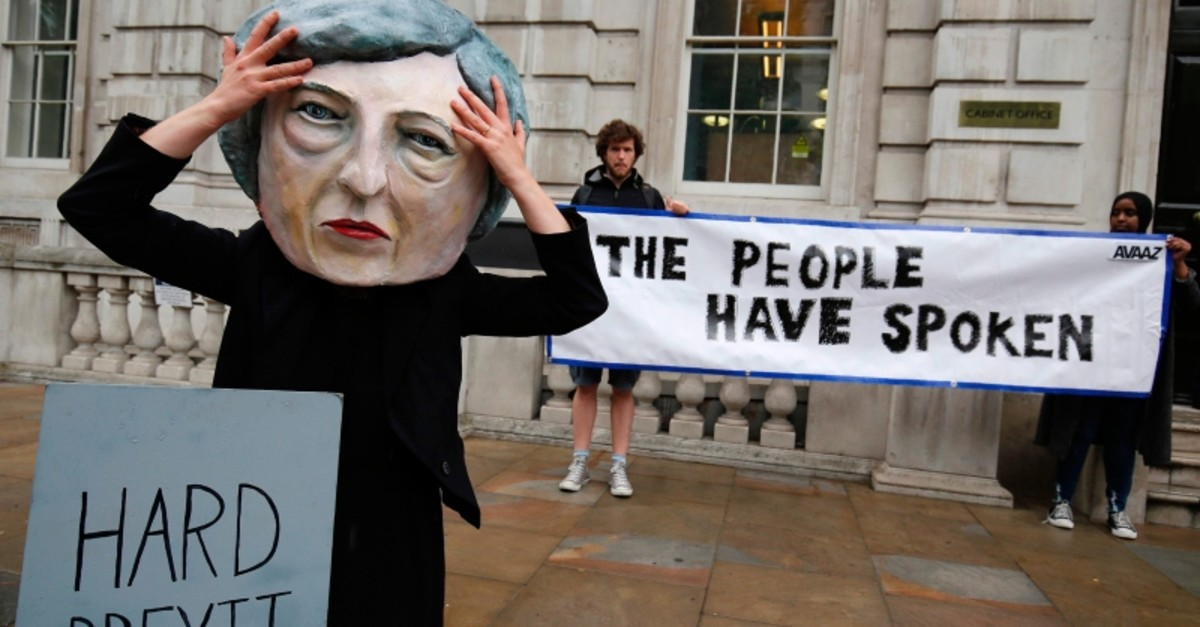 A demonstrator wears a mask depicting UK PM Nay, poses with a mock gravestone bearing the words u201cHard Brexit, RIPu201d, during a protest photocall near the entrance 10 Downing Street in central London on June 9, 2017 (AFP Photo)