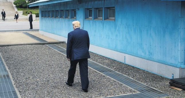 U.S. President Donald Trump walks to the line of demarcation to meet North Korea's leader Kim Jong Un in the Demilitarized Zone (DMZ), June 30, 2019.
