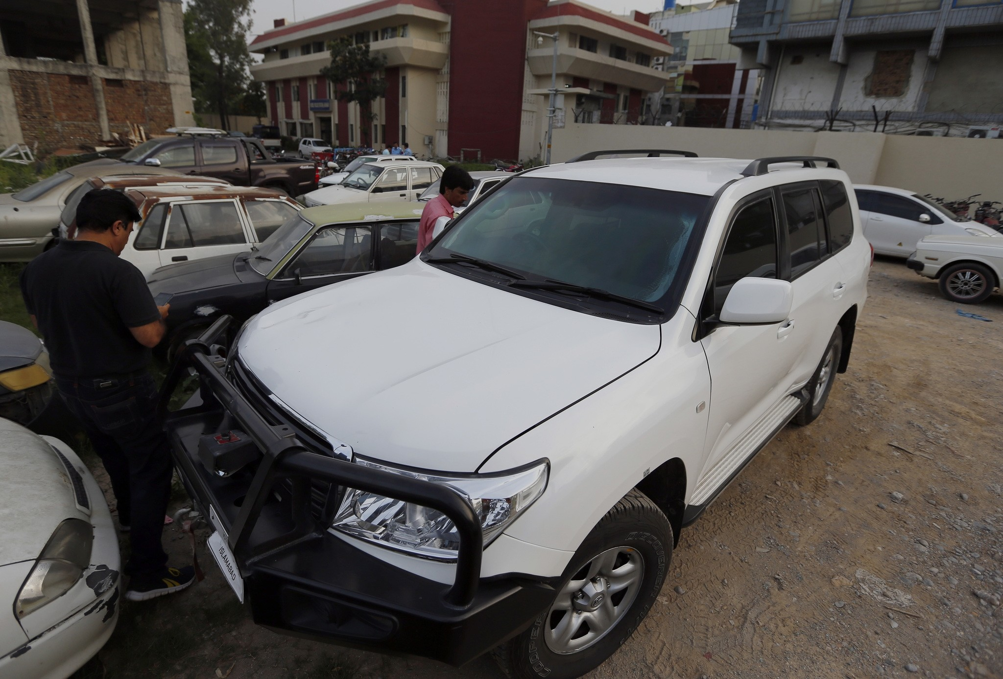 Pakistani journalists examine a car of American diplomate parked inside a police station after an accident in Islamabad, Pakistan, Saturday, April 7, 2018. (AP Photo)