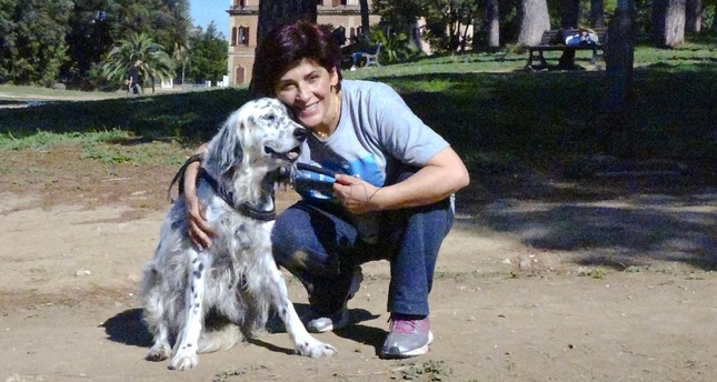 This undated photo made available Oct. 12, 2017, shows an Italian librarian who has won the right from her employer to use family sick leave to care for her ailing pet, posing with her dog Cucciola in a park in Rome. (AP Photo)