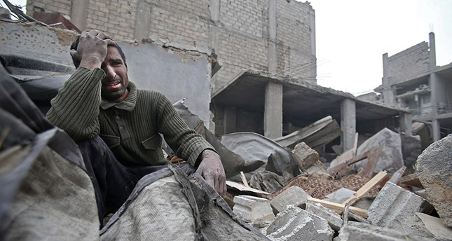 A Syrian man mourns over his destroyed home in the rebel-held besieged town of Arbin, in the eastern Ghouta region on the outskirts of the capital Damascus on February 5, 2018, following airstrikes. (AFP Photo)