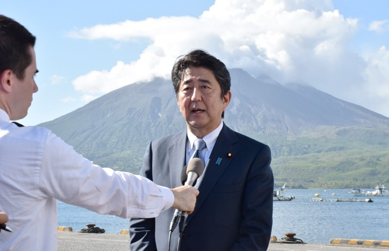 PM Shinzo Abe speaks as he announces his candidacy for the upcoming ruling LDP presidential election, during a press conference in front of Mount Sakurajima while on tour to Tarumizu, Kagoshima prefecture on Aug. 26, 2018. (Photo by JIJI PRESS / AFP)
