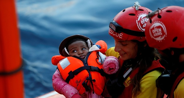 A crew member of MV Open Arms, the search and rescue ship of Proactiva Open Arms, carries a migrant baby before passing it to crew members of MV Aquarius Reuters File Photo
