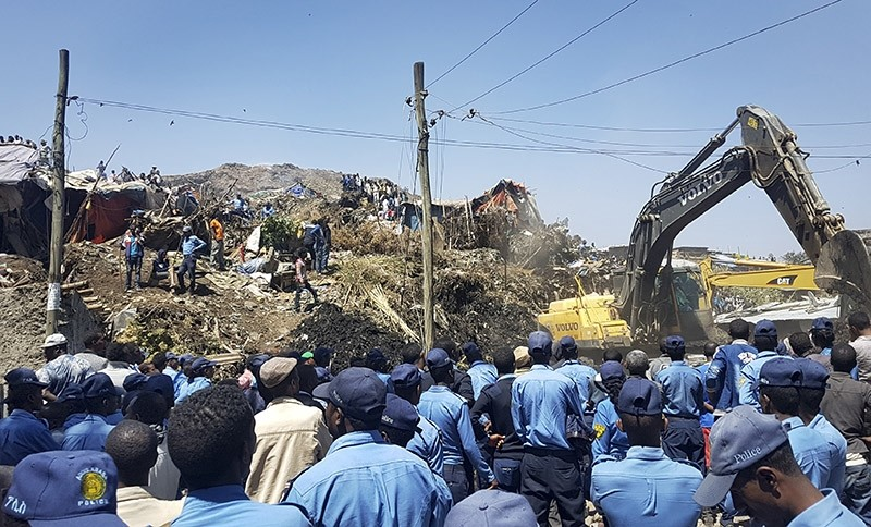 Police officers secure the perimeter at the scene of a garbage landslide, as excavators aid rescue efforts, on the outskirts of the capital Addis Ababa, Ethiopia Sunday, March 12, 2017. (AP Photo)