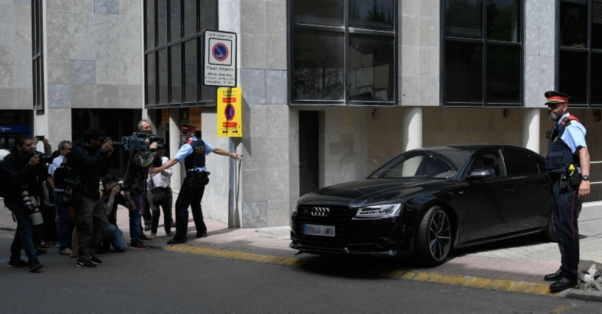 Journalists and Catalan regional police 'Mossos D'Esquadra' officers stand as a car carrying Colombian singer Shakira leaves a court in Esplugues Llobregat, near Barcelona. (AFP Photo)