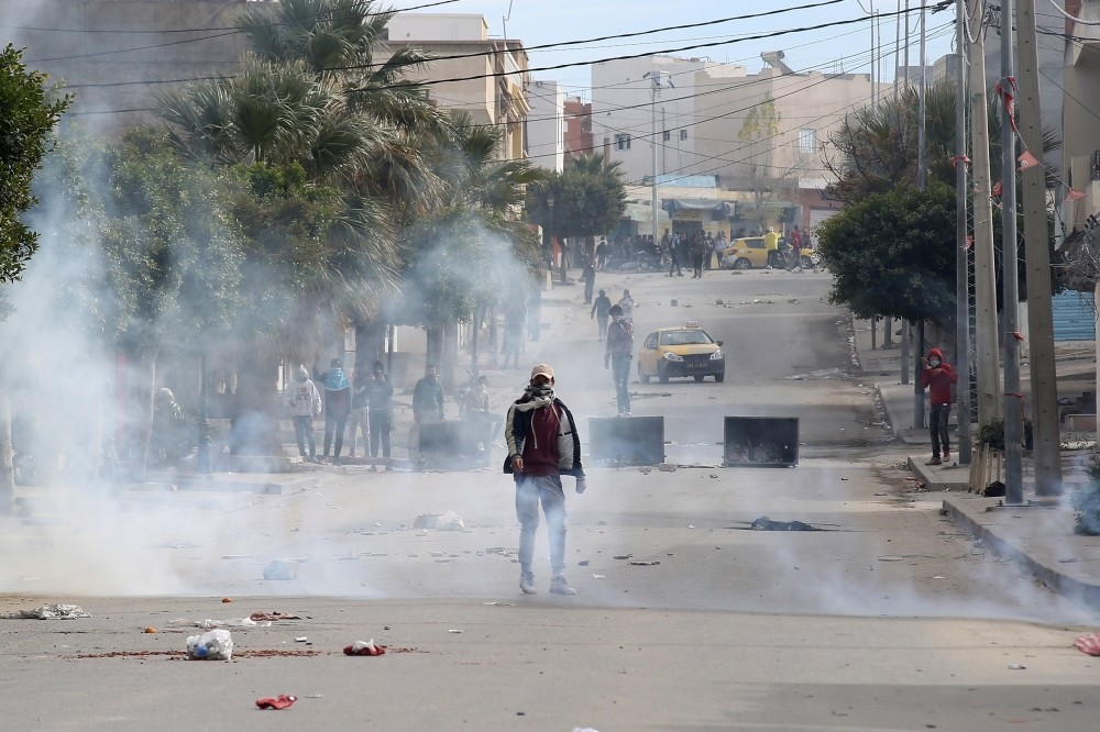 People take cover from tear gas grenades during clashes following protests, Kasserine, Dec. 25.