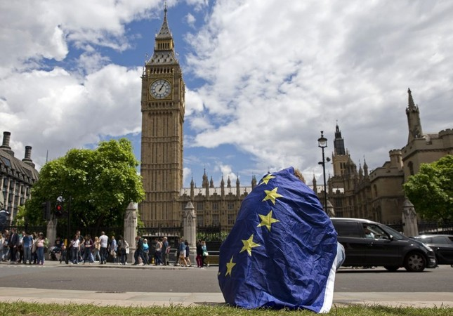 A demonstrator draped in an EU flag sits on the ground during a protest against the outcome of the U.K.'s referendum on the European Union.