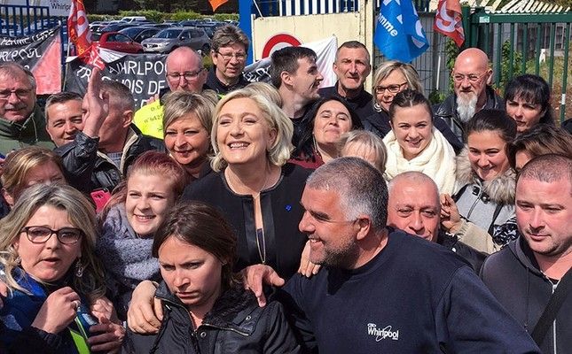 French presidential election candidate for the far-right Front National (FN) party, Marine Le Pen (C) smiles with people in front of the Whirlpool factory in Amiens, northern France, on April 26, 2017. (AFP Photo)