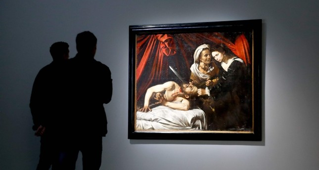 In this file photo taken on April 19, 2019 people watch Judith beheading Holofernes a 1607 painting from late Italian artist Caravaggio at the Kamel Mennour art gallery in Paris. (AFP Photo)