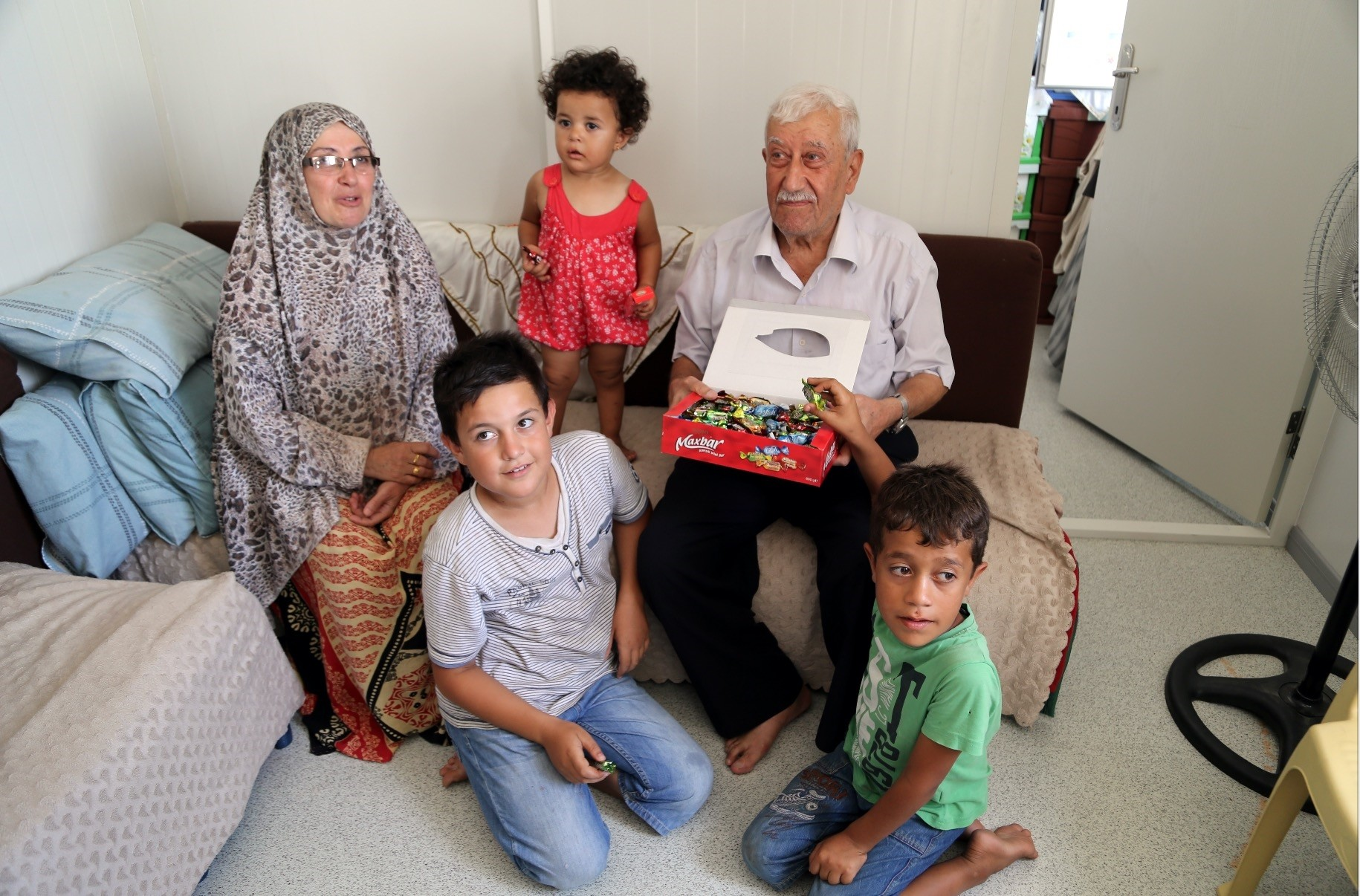 Muhammad Hasan Karrimo and his wife Melek hand out candy to their grandchildren who are among the few relatives they have in Turkey.