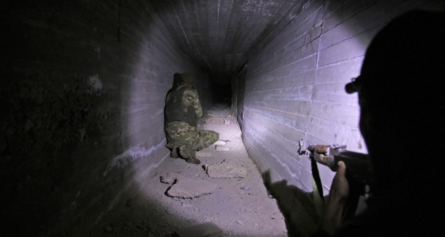 emTurkish-backed Syrian fighters inspect a tunnel, said to have been built by Kurdish fighters, in the Syrian border town of Tal Abyad, on October 21, 2019. (AFP Photo)/em