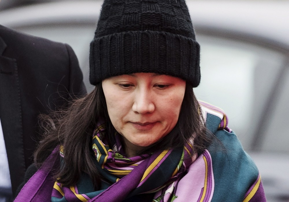 Huawei Chief Financial Officer Meng Wanzhou arrives at a parole office with a security guard in Vancouver, British Columbia, Dec. 12, 2018.
