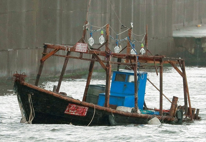 A wooden boat, which according to a police official carried eight men who said they were North Korean fishermen whose vessel ran into trouble, is seen near a breakwater in Yurihonjo, Akita Prefecture, Japan, Nov. 24, 2017. (Kyodo via Reuters)