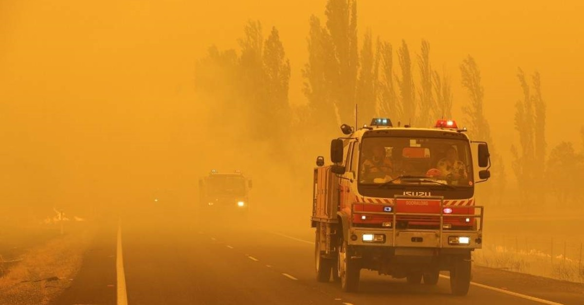 Fire burns in the grass along the road as firetrucks pass by near Bumbalong, south of the Australian capital, Canberra, Saturday, Feb. 1, 2020. (AP Photo)