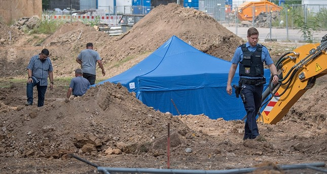 A policeman walks past a blue tent covering a British World War II bomb that was found during construction works on August 30, 2017 in Frankfurt am Main, western Germany. (AFP Photo)