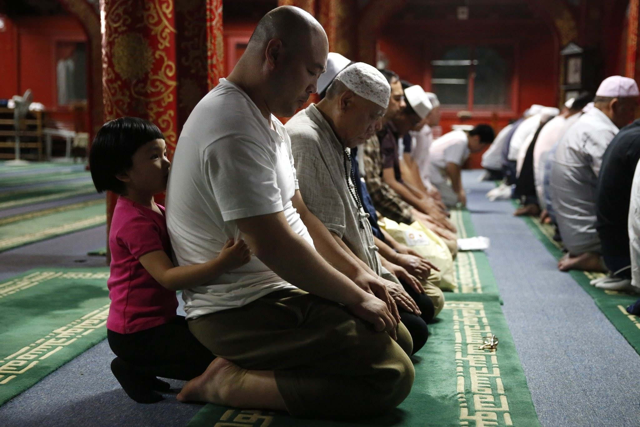 A little girl embraces a Muslim man from behind as he prays with other devotees during the evening ramadan prayers on the first day of the fasting month of Ramadan at the Niujie mosque in Beijing, China, 18 june 2015. (EPA Photo)