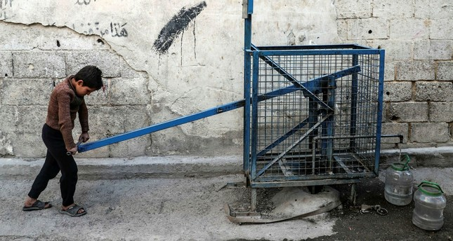 A boy uses a public hand-pump to collect water from a well in besieged East Ghouta, Syria, Oct. 18.