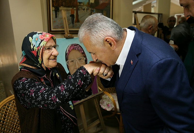 Yıldırım respectfully kisses the hand of an elderly woman during the Eid holiday.