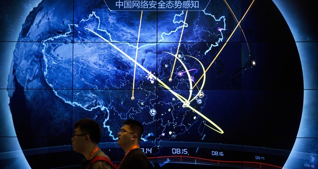 Attendees walk past an electronic display showing recent cyberattacks in China at the China Internet Security Conference in Beijing, Tuesday, Sept. 12, 2017. (AP Photo)