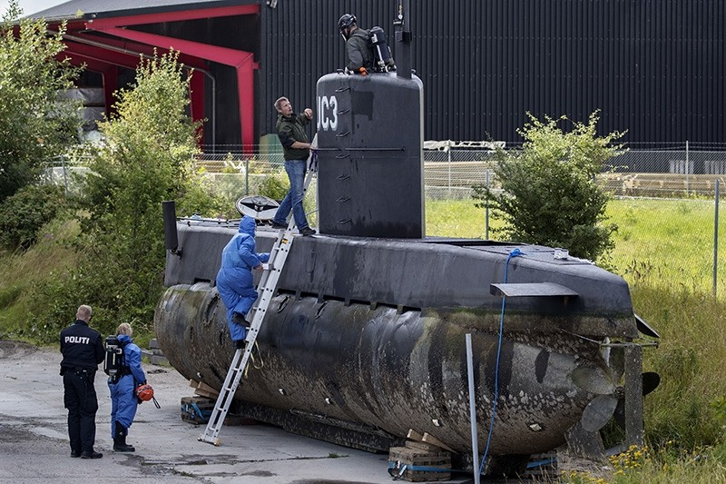 This is a  Sunday, Aug. 13, 2017, file photo of police technicians board Peter Madsen's submarine UC3 Nautilus on a pier in Copenhagen harbour, Denmark. (AP Photo)