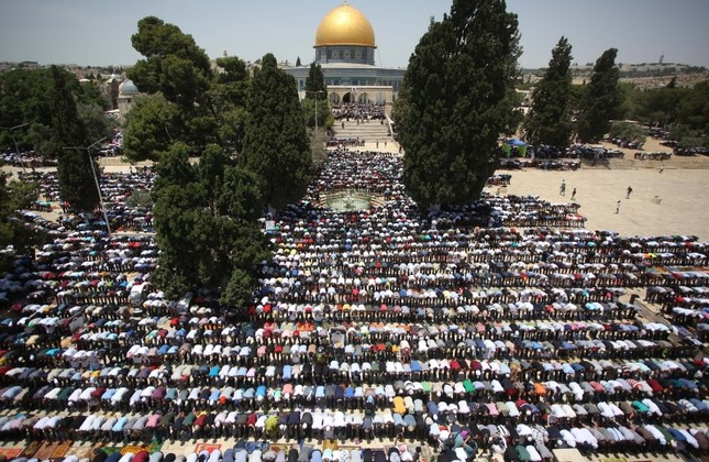 Palestinian men pray in front of the Dome of the Rock located on the opposite site of Al-Aqsa Mosque in the compound known to Muslims as Noble Sanctuary on the last Friday of the holy month of Ramadan, May 31, 2019. (AA Photo)
