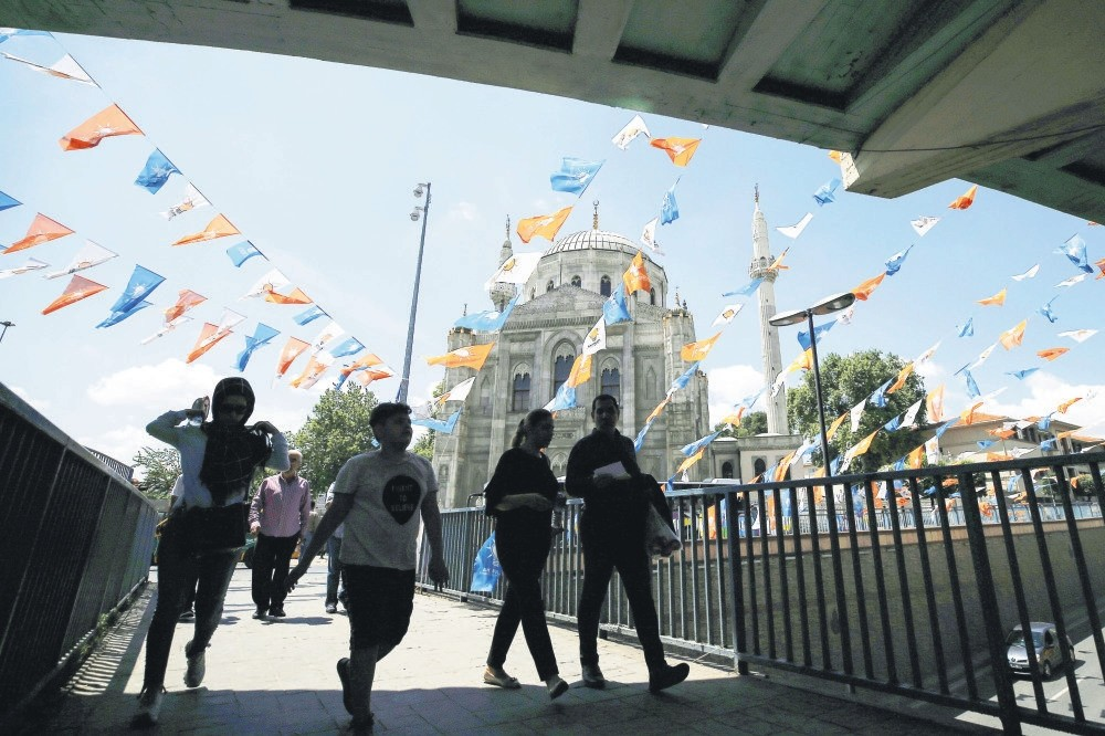 People walk under the ruling Justice and Development Party flags, Istanbul, June 20.