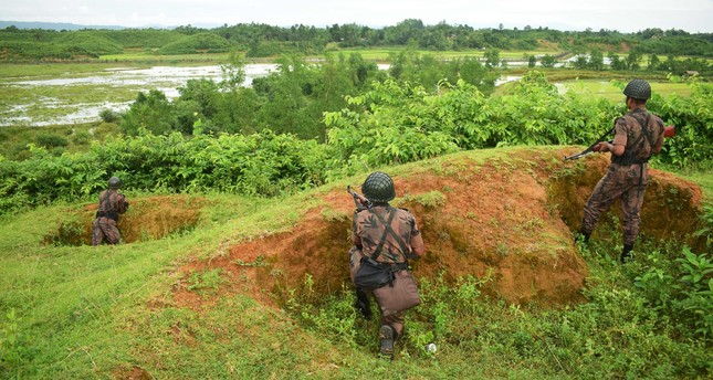 Border Guard Bangladesh (BGB) personnel stand alert as Rohingya people escape fresh gunfire at the Bangladesh-Myanmar frontier near Rakhine. Myanmar troops opened fire on hundreds of fleeing Rohingya villagers with mortar shells and machine guns.