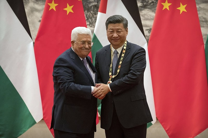 Palestinian President Mahmoud Abbas (L) shakes hands after presenting a medallion to Chinese President Xi Jinping (R) during a signing ceremony (EPA Photo)