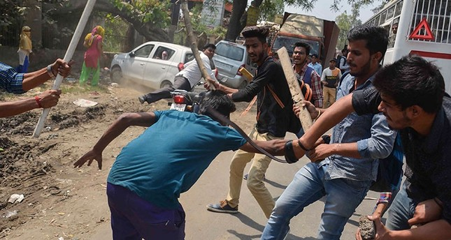 A protester (C) is beaten by Indian students after members of the Dalit community and other low caste groups threw bricks at their college during countrywide protests, in Meerut in Uttar Pradesh state on April 2, 2018.