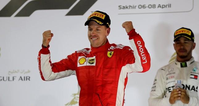 Ferrari's Sebastian Vettel celebrates winning the race as Mercedes' Lewis Hamilton looks on after Bahrain Grand Prix at Bahrain International Circuit, Sakhir, April 8.