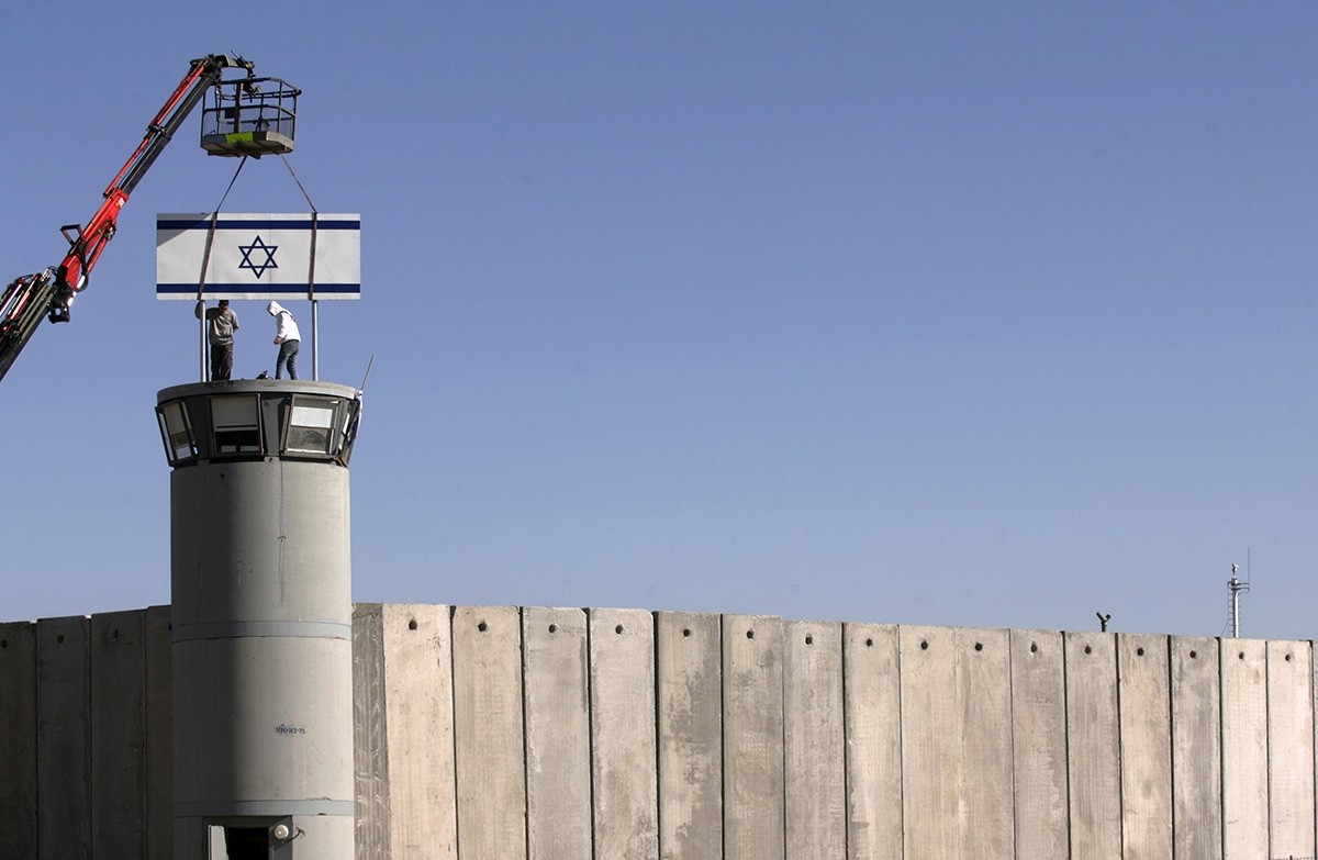 Workers place Israel's national flag atop a watchtower on the wall surrounding Israel's Ofer military prison near the occupied West Bank city of Ramallah Dec. 19, 2006. (Reuters Photo)