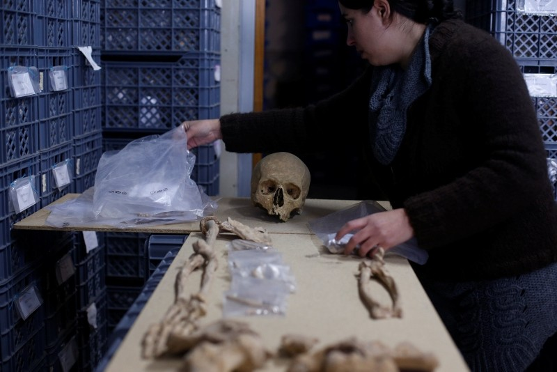 A person works on a skeleton from an ancient Roman cemetery with 2000-year-old skeletons and various artefacts, found below a restaurant in Lisbon, Portugal (Reuters Photo)
