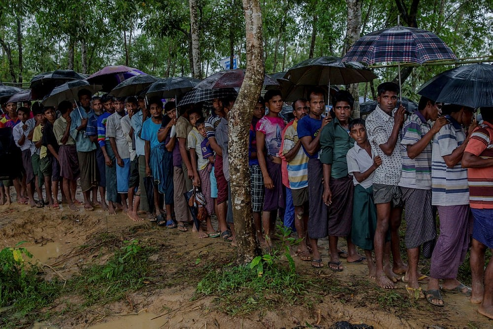 Rohingya Muslim men, who crossed over from Myanmar into Bangladesh, wait for their turn to collect a bag of rice distributed by aid agencies in, Bangladesh, Sunday, Sept. 17, 2017. (AP Photo)