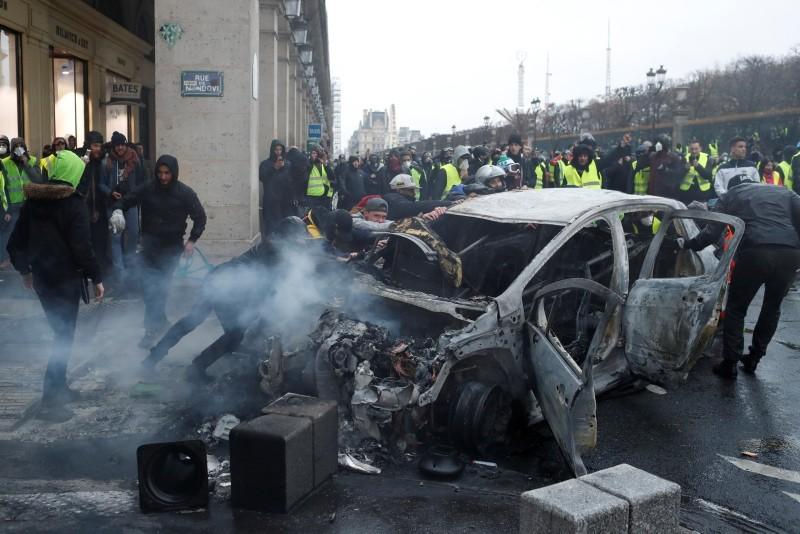 Demonstrators push charred car during a demonstration Saturday, Dec.1, 2018 in Paris. (AP Photo)