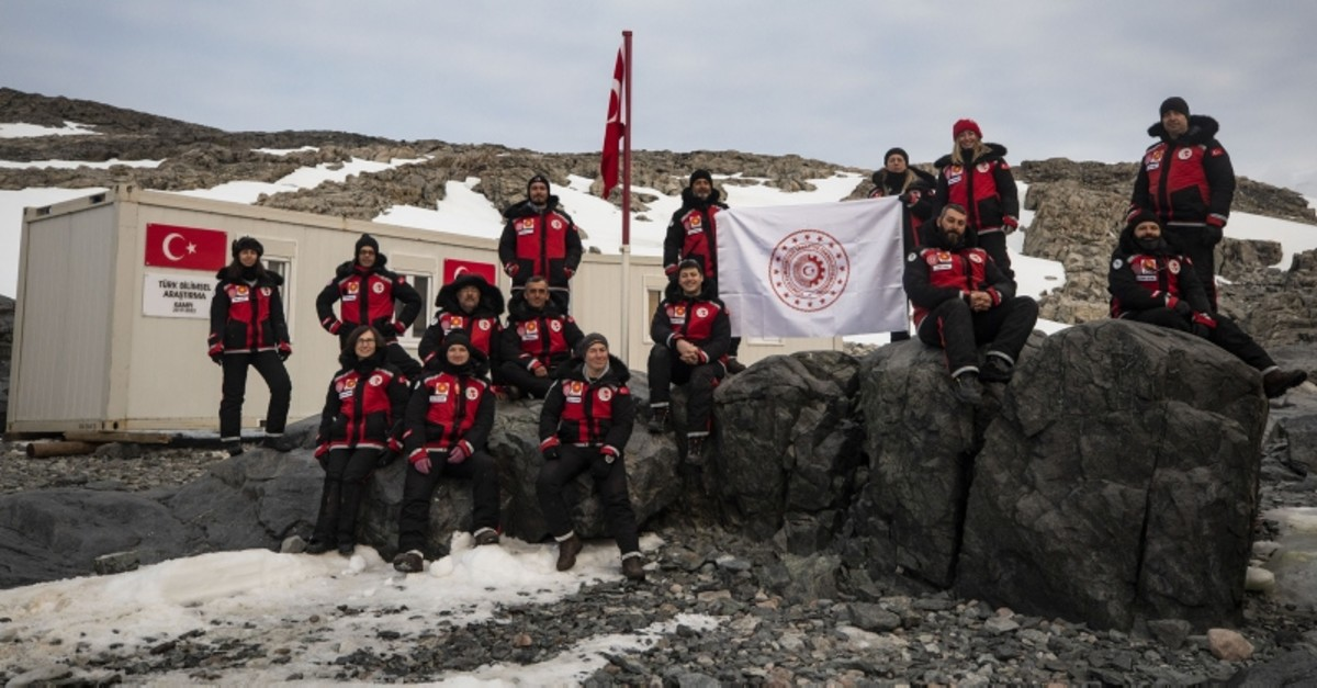 Turkish researchers pose in front of temporary base established on Horsheshoe Island, Antarctica. (AA Photo)