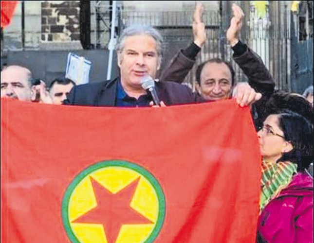 Anrej Hunko poses with a PKK banner, the terror group outlawed by the EU.