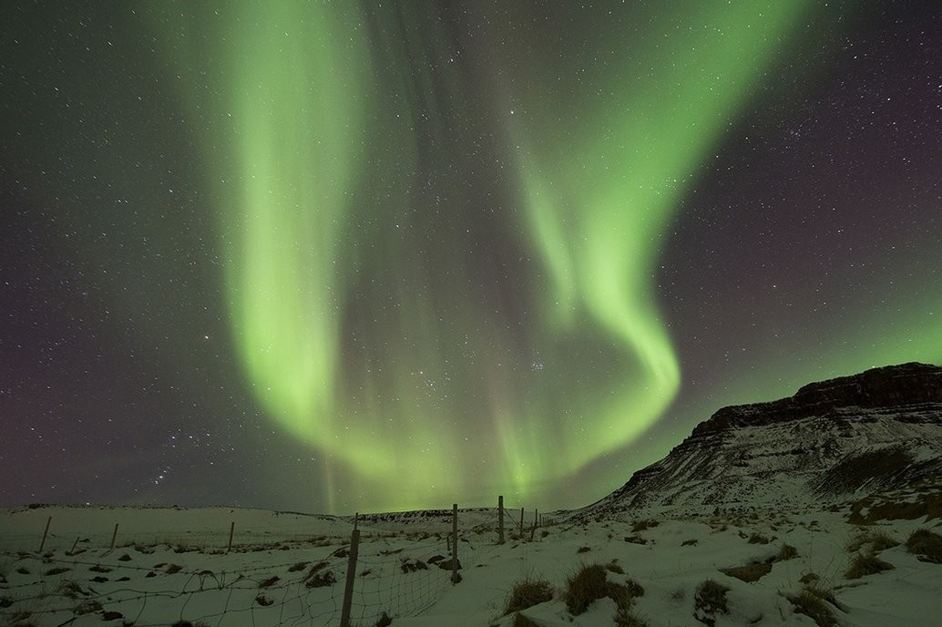 The Northern Lights, or the aurora borealis, appear in the sky over Bifrost, Western Iceland.