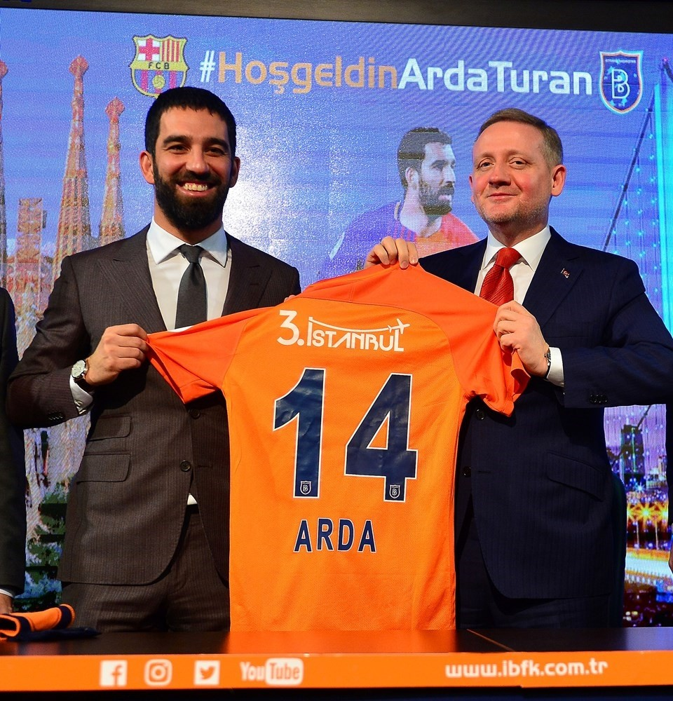 Arda Turan (L) poses with the jersey of his new team Bau015faku015fehir next to club President Gu00f6ksel Gu00fcmu00fcu015fdau011f during a press conference in Istanbul.