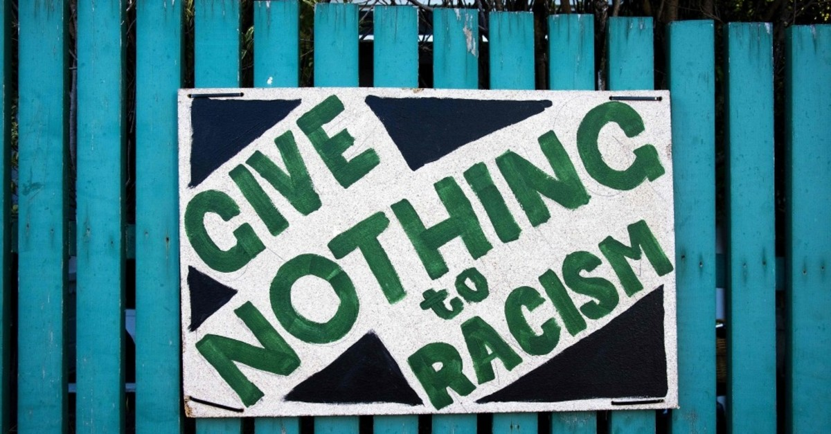 A placard that reads ,give nothing to racism, is seen on a picket fence in Wellington on March 22, 2019, a week after the twin mosque massacre in Chrishchurch, New Zealand.