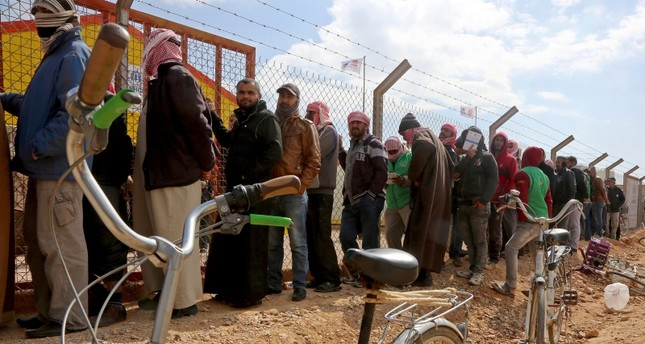 In this Feb. 18, 2018 file photo, Syrian refugees line up to register their names at an employment office, at the Azraq Refugee Camp, 100 kilometers (62 miles) east of Amman, Jordan (AP Photo)