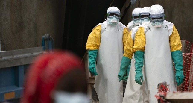 FILE - In this Tuesday, July 16, 2019 file photo, health workers dressed in protective gear begin their shift at an Ebola treatment center in Beni, Congo DRC.  (AP Photo)
