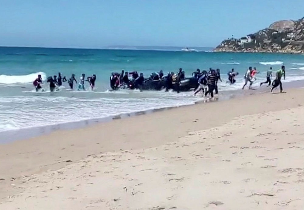 Migrants scatter as a rubber dingy lands on a beach at Cadiz, southern Spain, Aug. 9.